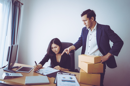 Boss pointing finger to pressure a female office worker Stock Photo