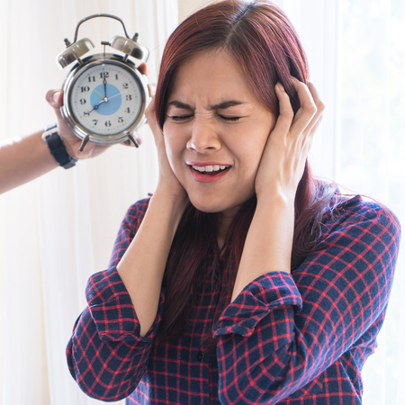 Woman cover her ear from stress out by Alarm clock deadline sound