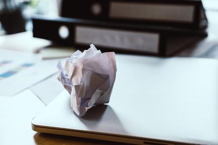 オフィステーブルのラップトップ上のスクラップ紙ボール