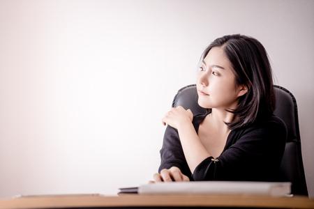 ビジネスウーマンは、オフィスチェアで彼女の肩を休ませ、マッサージしています