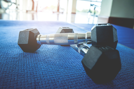 Pair of dumbbell on a fitness floor silhouette from windows light