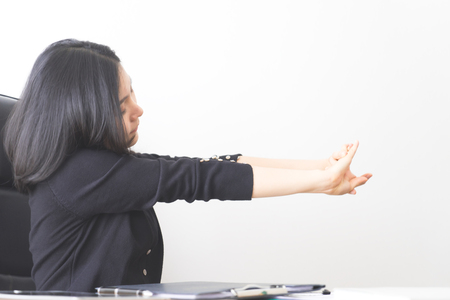 Asian female office worker is stretching arm in office