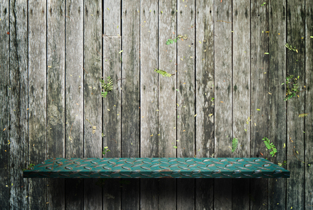 Green metal shelf display counter on wooden wall Reklamní fotografie - 95800011