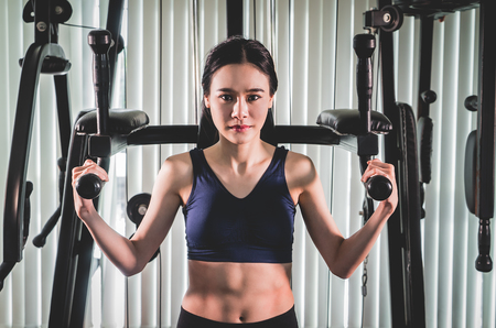 Strong asian woman is training on fitness gym machine 스톡 콘텐츠