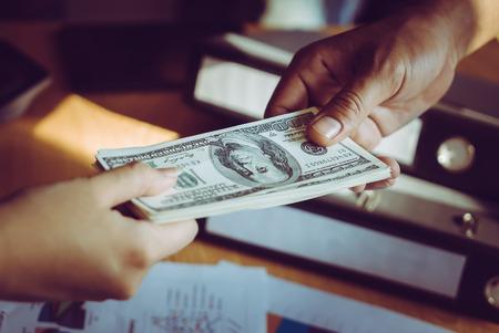 Business man hands handing money over a business dealing