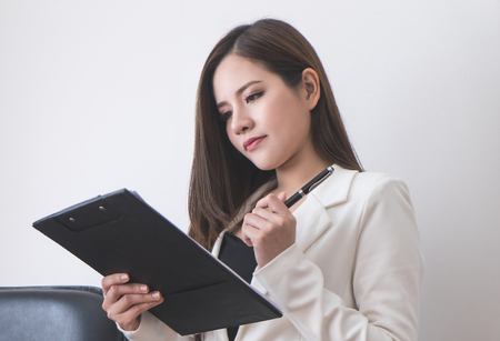 Asian Business woman is looking at notepad