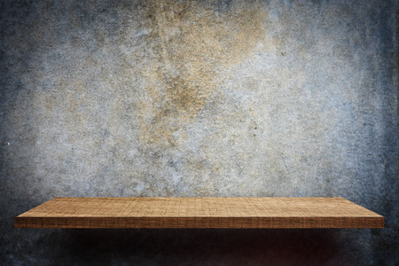Blank wooden display shelf on dark cement wall Stock Photo