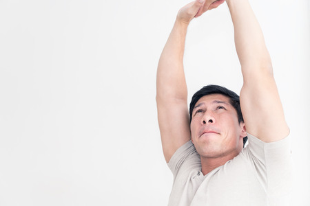 Asian male is stretching his arm out