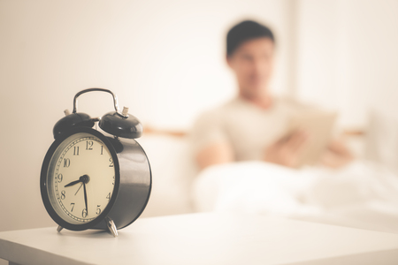 Alarm clock on bedside table with awake person reading