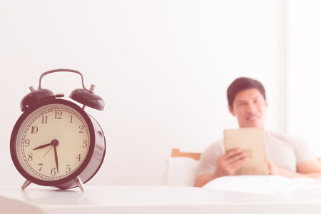 Man is reading book in morning alarm clock show 8 o clock Imagens - 99348689
