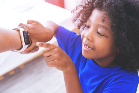 Little African kid is playing with smartwatch on adult wrist Banque d'images