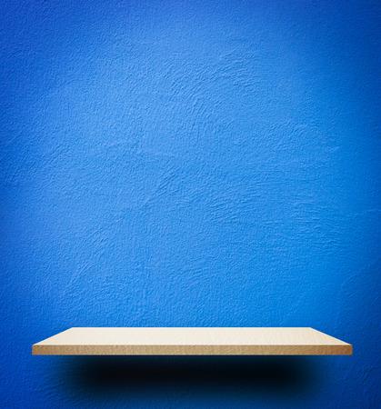 Empty wooden shelf on blue wall background