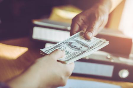Business man hands handing money over a business dealing Standard-Bild - 97372400