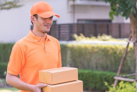 Delivery man in orange bringing in customer the package