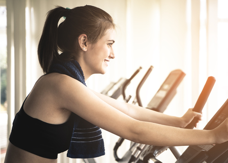 Happy Woman is exercising on a fitness bike machine