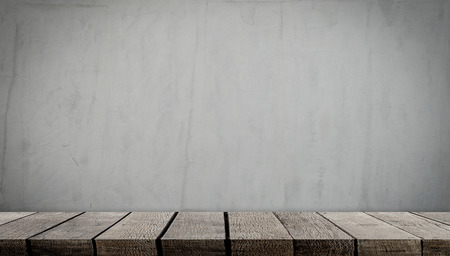 Blank wooden display table on gray cement wall