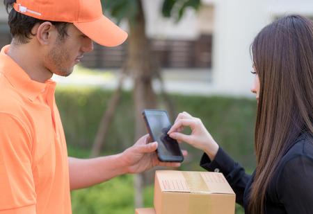 La donna di affari sta firmando sul dispositivo mobile che riceve la consegna del pacchetto