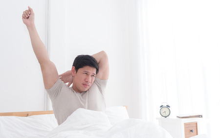 Asian male is stretching out after woke up on bed 스톡 콘텐츠