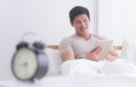 Man using tablet in morning bed with alarm clock counting late