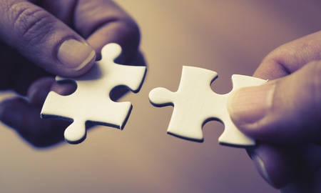 Two hands joining together two jigsaw puzzles Banco de Imagens