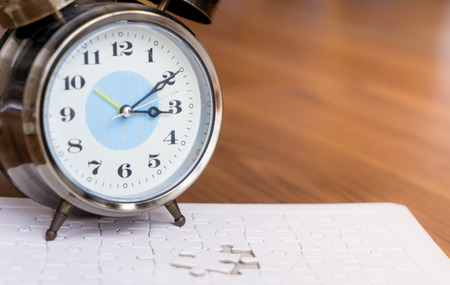 Time counting down on alarm clock to palce the last jigsaw Reklamní fotografie