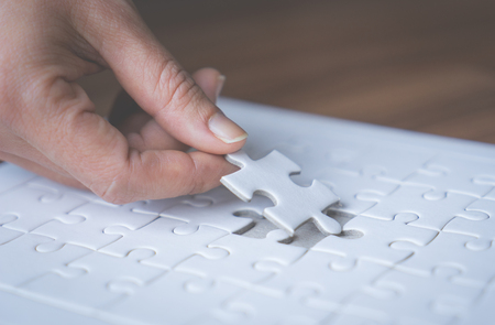 Hand placing the last jigsaw for business solution concept