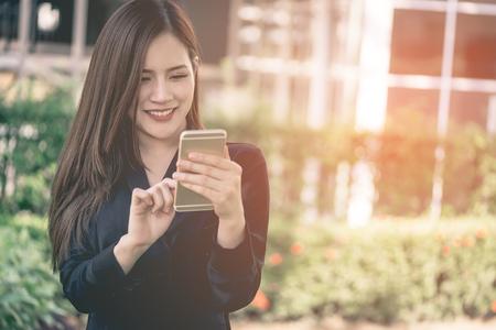 かわいいアジアの女性は、都市公園でモバイル上でテキストメッセージです