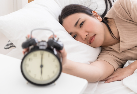 Asian woman on bed reaching out to stop the alarm clock