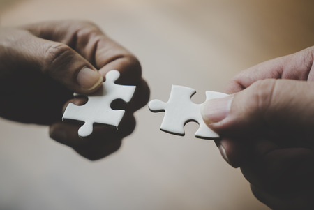 Two hands joining together two jigsaw puzzles Stockfoto