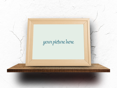 Empty wooden frame mock up on shelf with cracked white wall