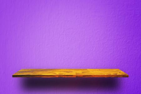 Empty wooden shelf on purple cement wall