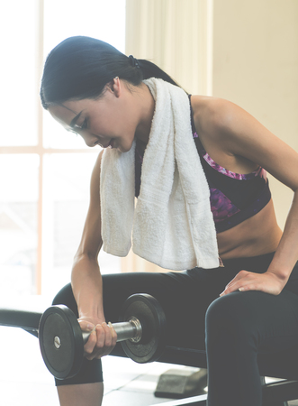 Asian woman is lifiting dumbbell in fitness