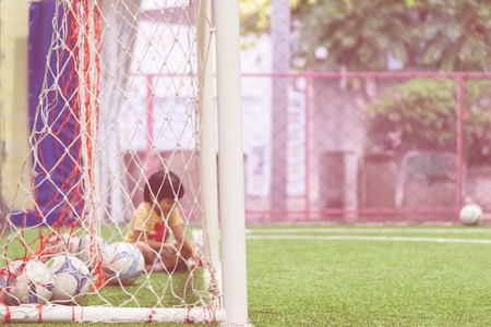 Little kid is sitting in the soccer goal Stockfoto - 99622325