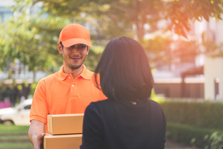 Delivery man in orange is handing packages to a woman