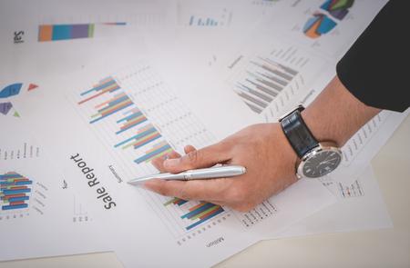 Homme d & # 39 ; affaires marquage sur les feuilles de données en utilisant le stylo métallique Banque d'images - 99597346