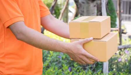 Delivery man in orange is handing packages