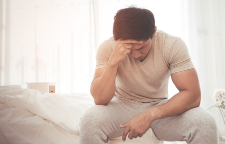 Asian male woke up on bed with headache and stress out