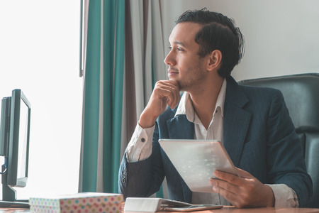Dreamy smiling business man happily looking out the windows