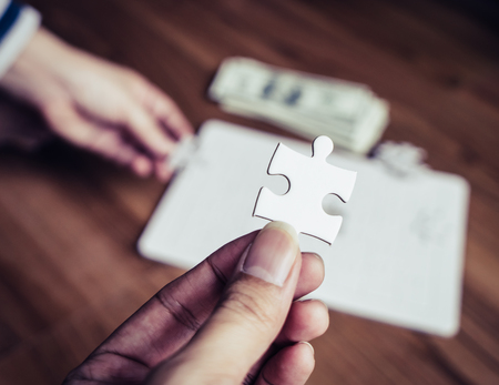 Hand holding the last right jigsaw for business competitive solution concept