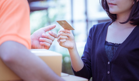 Woman is using credit card to pay for online delivery