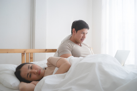 Angry wife on bed when husband is ignoring her but go online on computer