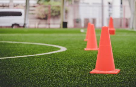 Orange Fußballtrainingskegel im Fußballtrainingsplatz Standard-Bild