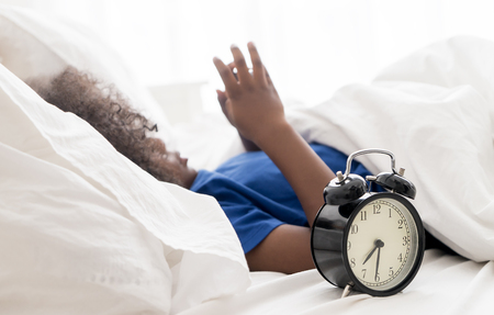 Little kid using smartphone with alarm clock counting too much time in the morning Stock Photo