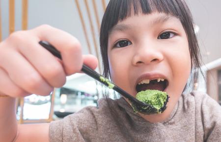 Asian girl eating Japanese green tea matcha ice cream