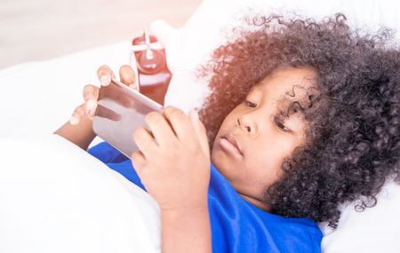 Little kid is playing with mobile phone on bed with alarm clock Stockfoto