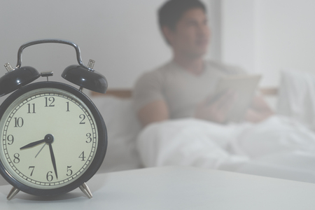 Man in morning bed with alarm clock counting late Stock Photo