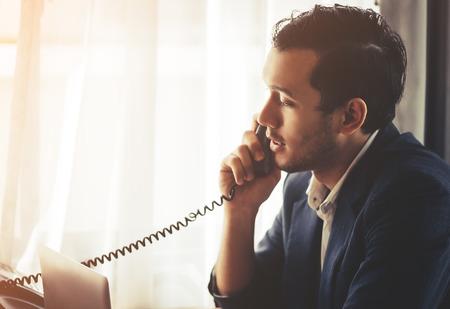 De zakenman doet bellen op de vaste lijn van de Fax-telefoon