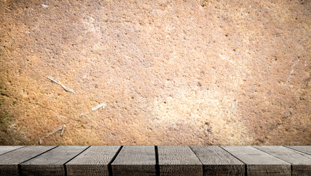 Blank wooden display shelf on brown cement wall Stock Photo