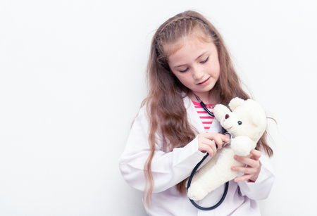 Little kid is using Doctor suit and equipment to check Teddy bear health Stock Photo