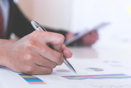 Business man marking on data sheet using metal pen Banque d'images - 101487674
